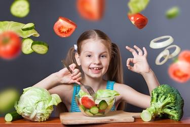 Bambina e verdura ricca di fibre